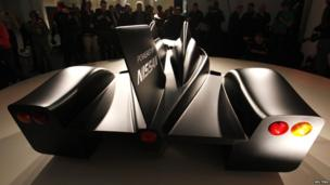 Nissan's new Deltawing race car is seen after it was unveiled in London. This rear shot of the car shows a black tail fin. The red brake light and amber indicators are illuminated by the artistic lighting which shows off the smooth contours of the race car.