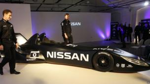 Nissan's new Deltawing race car is seen after it was unveiled in London. The black, sleek sports car has a very long fuselage. The car is unveiled at a press event and people can be seen celebrating, shrouded in purple light.