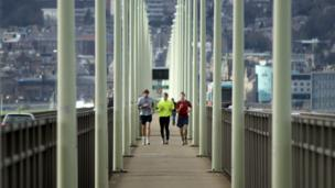 Runners on the pedestrian walkway of the Tay Road Bridge