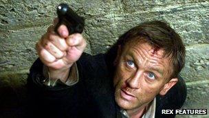 Daniel Craig aiming a gun in character as the fictional spy James Bond