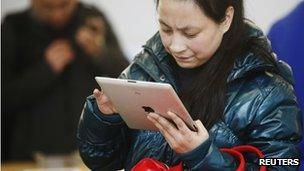 A woman tries out an iPad at an Apple stores in China