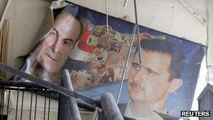 A damaged picture of the late Hafez al-Assad and his son, President Bashar al-Assad, in a police building damaged by an explosion in Damascus (17 March 2012)