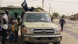 In this Saturday, 14 April, 2012 photo, fighters from the Ansar Dine group, flying the group's black flag, instruct local residents in how to follow Shariah, as they stop in a market area of Timbuktu, Mali.