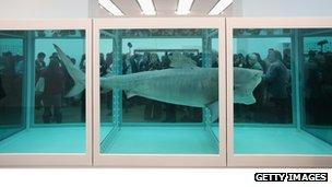 Members of the public view artwork by Damien Hirst entitled 'The Physical Impossibility of Death in the Mind of Someone Living' in the Tate Modern art gallery.