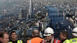 Workers stand in front of a picture of the Shard