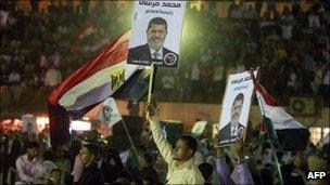 Supporters hold posters and flags at a rally for Mohammed Mursi at a football stadium on 23 April