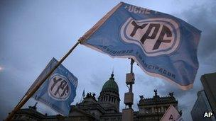"""Supporters of an oil nationalization bill proposed by Argentina's President Cristina Fernandez holds up flags reading in Spanish """"Fight and return YPF"""" outside Congress"""