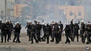 Riot police fire tear gas chase anti-government protesters during clashes in Sanabis, Bahrain (24 April 2012)