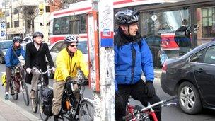 Cyclists wait in traffic