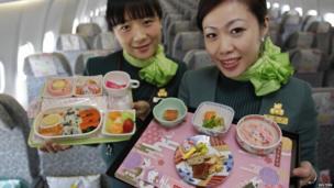 Two flight attendants holding the on board food