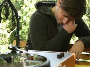 Musician and song-writer Adam Arcuragi listens to a newly minted vinyl recording