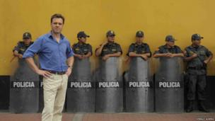 Prof Niall Ferguson stands in front of a row of policemen