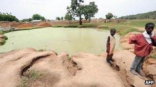 Two young boys stand in front of a pond infected with lead poison at Dareta village, Anka district in Zamfara State on 10 June 2010