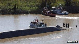Rescuers climb on the capsized Argentine ship on the River Paraguay