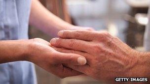 A nurse holding a patient's hand