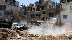 Workers clear debris left by the attack in Damascus on 10 May