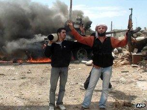 Free Syrian Army fighters celebrate destroying government weaponry near Rastan (14 May 2012)