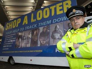 """Officer with Greater Manchester Police's """"Shop a Looter"""" billboard"""