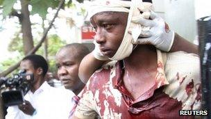 A man injured during an explosion is assisted from the scene in Kenya's capital Nairobi, May 28, 2012.