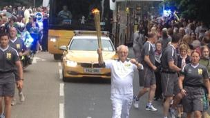 Ronald Price, sy'n 83 oed, oedd un o'r cludwyr drwy Wrecsam. Mae'n weithgar yn ei gymuned yn Llandrillo-yn-Rhos