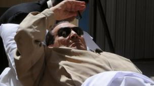 Ousted Egyptian president Hosni Mubarak gestures as he is wheeled out of a courtroom following his verdict hearing in Cairo