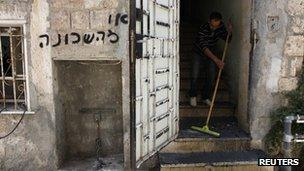 """A man clears debris from the entrance to a flat in Jerusalem following a suspected arson attack. The grafitti says: """"Get out of the neighbourhood"""" (4 June 2012)"""