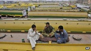 Pakistani drivers drink tea on top of an oil tanker, which was used to transport Nato fuel supplies to Afghanistan but is now parked with other tankers in a compound in Karachi. June 4 2012