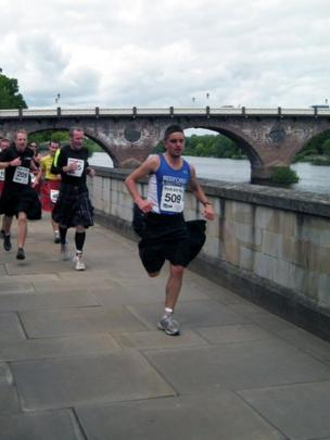 Men in kilts running in Perth