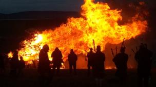 Pipers silhouetted by a bonfire of burning pallets