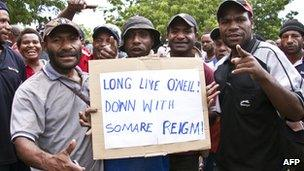 Protesters hold a placard during a friendly demonstration in Port Moresby, 15 Dec 2011