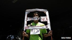 """student from the anti-PRI youth opposition movement """"Yosoy132"""" (I am 132) holds a mock TV during a protest at the facilities of telecoms regulator Cofetel"""