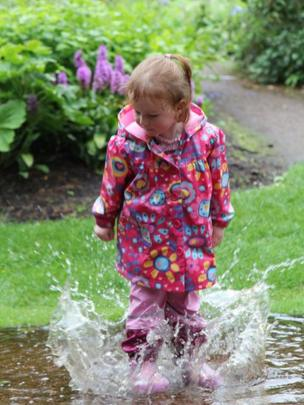 Elizabeth splashes in a puddle