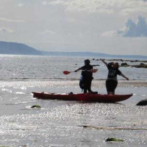 Women standing by a canoe on West Kilbride beach