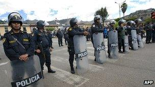 Riot policemen stand guard as thousands of residents march in Cajamarca on 29 May, 2012