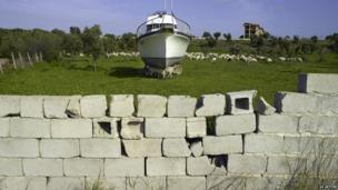 """Image from """"Moments Before the Flood"""" photograph series, showing a boat behind a wall in Italy"""