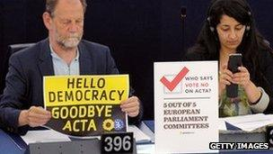 """Member of European Parliament holds sign reading """"Hello democracy, goodbye Acta"""""""