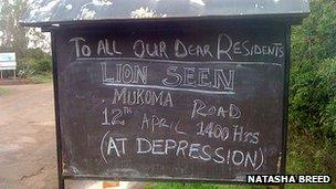 Sign by roadside warning of lions in the area