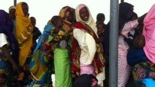 Women holding babies queuing at a clinic