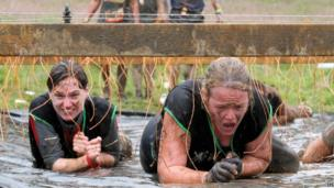 Two women crawl in the mud