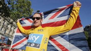 Bradley Wiggins, winner of the 2012 Tour de France cycling race holds the Union flag aloft during a parade after the last stage of the race in Paris, France.