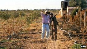 A handout picture released by the Syrian opposition's Shaam News Network on 4 July 2012 shows Syrian rebels walking in a field in Qusayr near Homs, on 3 July
