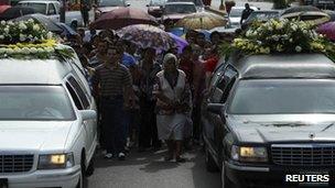 People walk in a funeral cortege in Muzquiz, Mexico