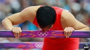 China's Liu Xiang kisses a hurdle after falling while competing in the men's 110m hurdles heats at the athletics event of the London 2012 Olympic Games on 7 August, 2012