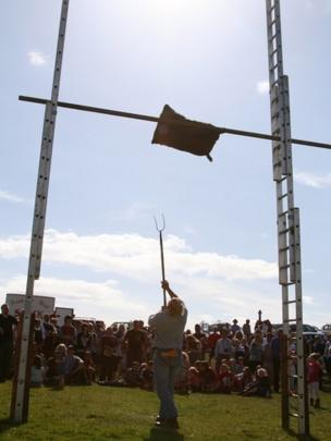 Man tosses a sack into the air using a pitchfork