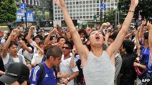 Japanese football fans in Tokyo celebrate after the women's football team won a silver medal against the US