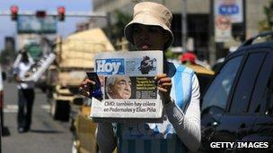 A newspaper seller displays a copy of the Dominican newspaper Hoy in Santo Domingo