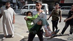 """A Syrian man carries a wounded girl into a hospital in Aleppo, Syria""""s second largest city, on August 28, 2012"""