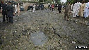 Security officials and residents gather near a crater caused by a bomb attack in Peshawar on Monday