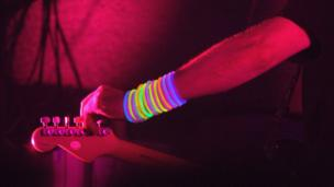 A guitarist with day glow wrist bands tunes his guitar