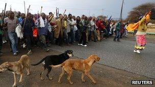 "Striking mineworkers march outside Lonmin""s Marikana min"